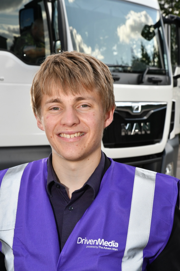 Ed Hollands stand in front of a white truck cab.