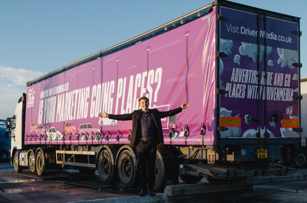 Dragon's Den Winner Ed Holland stands in front of a fully wrapped branded truck