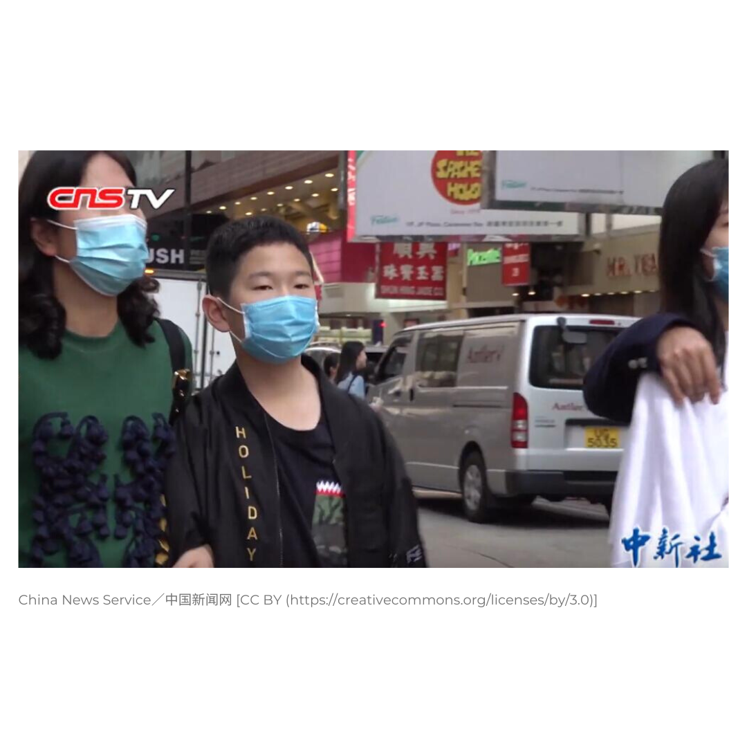 photo of people in Asian city walking down the street wearing facemasks.